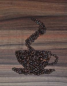 Kaffebönor på ett bord är formade till en kaffekopp, med ångande hett kaffe i. CC0 Public Domain, pixabay.com